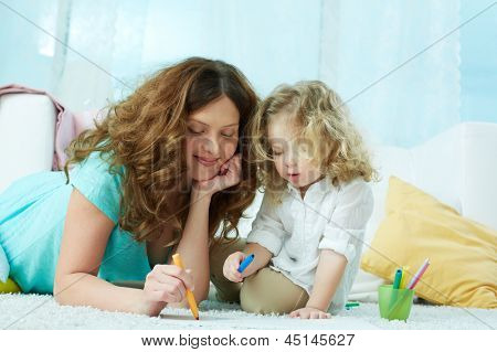 Close-up image of a lovely mom drawing with her little daughter