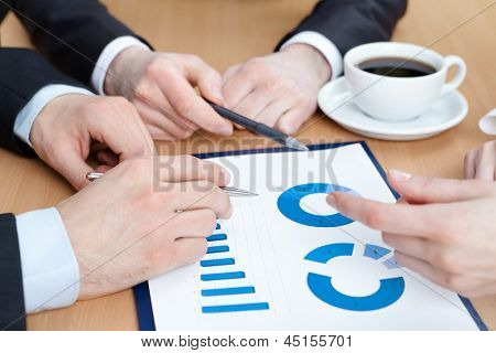 Close up of hands of managers discussing diagram and sitting at the table with cup of coffee