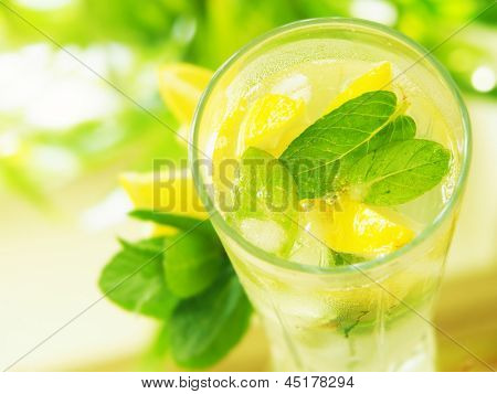 a glass  water with lemon and mint