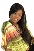 A young African-American woman in a tie dye blouse leans on her arm and smiles pleasantly. poster