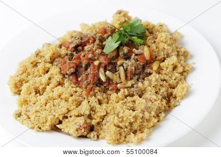 A plate of Lebanese burghul bi banadoura, or cracked wheat with tomatoes. The dish incorporates onion, minced meat and pine nuts, along with the burghul or bulgar wheat.