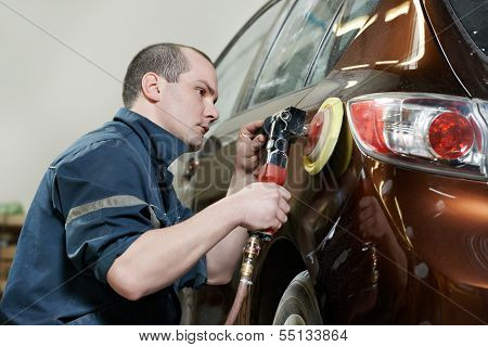 auto mechanic worker polishing bumper car at automobile repair and renew service station shop by power buffer machine