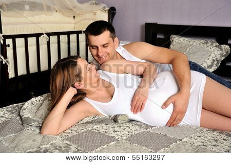 poster of Happy couple future parents relaxing at home on a bed.