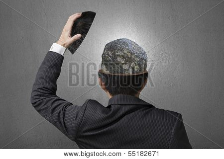 Hard Stone Covered With Lines Inside Businessman Head In Gray Concrete Wall Background