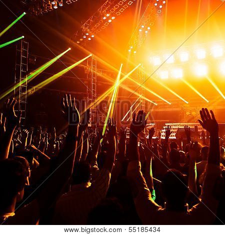 Photo of young people having fun at rock concert, active lifestyle, fans applauding to famous music band, nightlife, DJ on the stage in the club, crowd dancing on dance floor, night performance