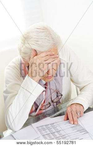 Unhappy senior woman looking at financial bill on the table