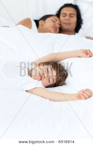 Parents And Their Son Sleeping On The Bed