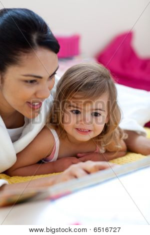 Caring Mother Reading A Book With Her Girl