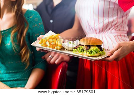 Friends or couple eating fast food in American fast food diner, the waitress wearing a short costume