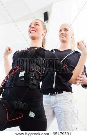 Female personal trainer giving man ems electro muscular stimulation exercise