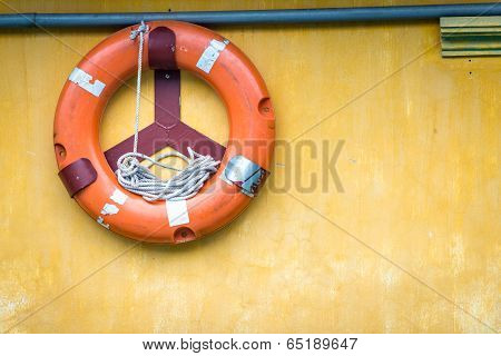 Orange Old Lifebuoy With Rope Attached To Wall.