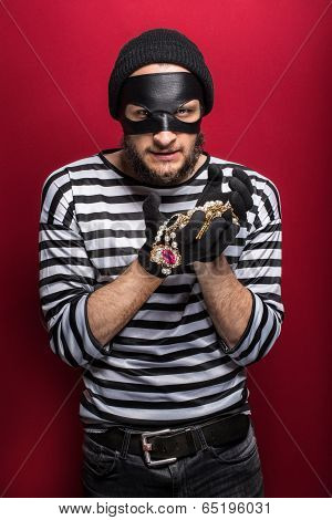 A thief holding stolen necklace