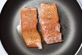 Preparing healthy salmon lunch in a frying pan poster