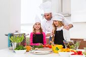 Chef master and junior pupil kid girls at cooking school with food on countertop poster