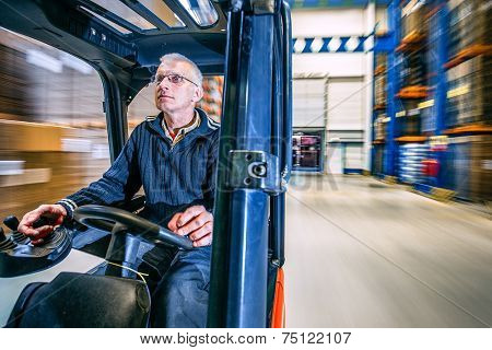 man driving a forklift through a warehouse in a factory