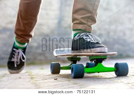 Skateboarder setting his board in motion by pushing off with one foot in an urban setting, representing the youth (sub) culture