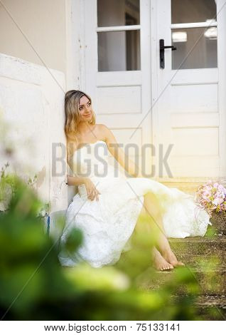 Blonde bride by old house
