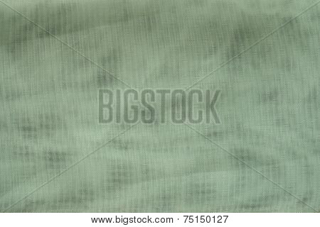the textured background of green color with tone spots from synthetic fabric in a grid with small cells poster