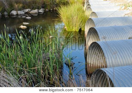 Drainage Pipes Flowing Into Green Pond