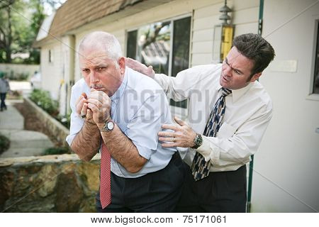 Mature businessman with a bad cough.  His friend and colleague is worried about him and pats him on the back trying to help.  Vignette added.