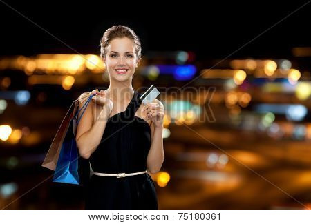 shopping, sale, banking, money and holidays concept - smiling woman in dress with shopping bags and credit card over black background poster