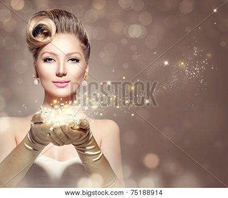 Holiday Retro Woman with magic in her hand. Beauty Fashion Christmas Vintage Style Lady with Beautiful Luxury Hairstyle, makeup, accessories. Golden Silk Gloves and dress