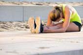 Young, very flexible woman in sportswear, touching her knees with her nose. She's stretching her muscles during a training run on the beach boulevard on a sunny summer evening. poster