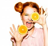 Beauty Model Girl with Juicy Oranges. Beautiful Joyful teen girl with freckles, funny red hairstyle and yellow makeup . Professional make up. Orange Slices. Isolated on a white background  poster