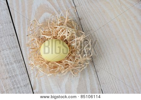 Overhead shot of a yellow dyed Easter Egg in a nest made of raffia on a rustic white wooden kitchen table. Horizontal format.