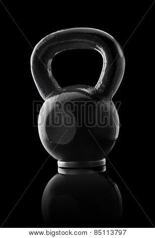 Black metallic kettlebell on black reflective background.