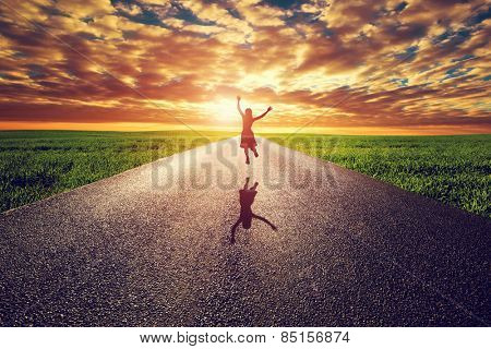 Happy woman jumping on long straight road, way towards sunset sun. Travel, happiness, win, healthy lifestyle concepts. poster