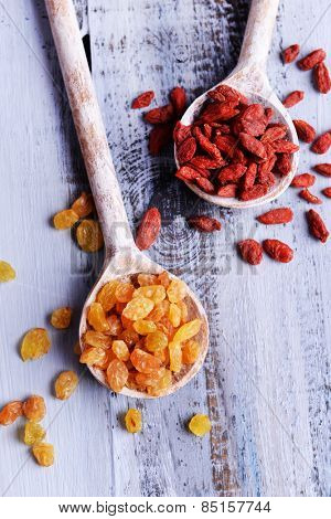 Raisins and Goji in spoons on color wooden table background