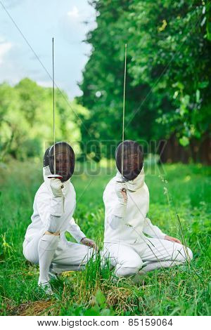Two fencers women squatting down with rapiers pointing up ready for competition