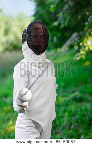Fencer woman staying over beautiful nature background with rapier