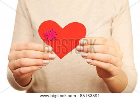 Woman holding broken heart with patch close up