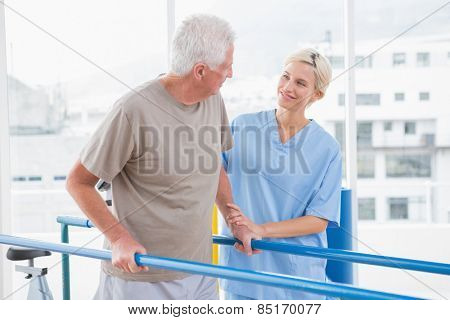 Senior man walking with therapist help in fitness studio