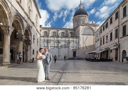 DUBROVNIK, CROATIA - MAY 28, 2014: Groom and bride posing in front of the Rector Palace. Streets of Dubrovnik's Old town are very popular for wedding photo sessions.