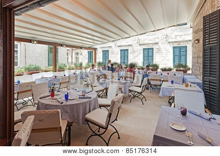 DUBROVNIK, CROATIA - MAY 27, 2014: Waitress serving guests at restaurant's terrace. Dubrovnik has many restaurants which offer traditional Dalmatian cuisine and some great wine lists.