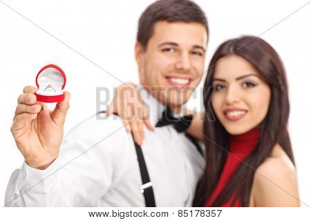 Man and his fiancee showing their engagement ring with the focus on the ring isolated on white background