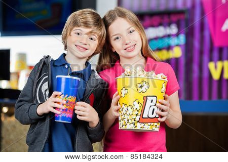 Portrait of happy brother and sister holding snacks against cinema concession stand