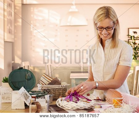 Happy casual caucasian blonde mid adult housewife making valentine day wreath at home. Smiling, wearing glasses, standing at table, do it yourself, gift, present.