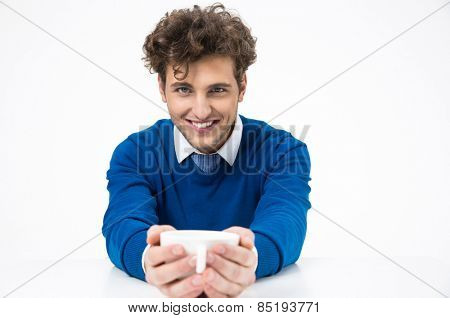Happy businessman sitting at the table and holding cup of coffee