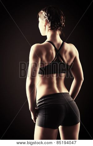Slender young woman with an athletic physique standing back. Fitness sports. Healthcare, bodycare. Black background.