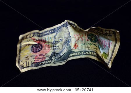 A crumpled US Ten Dollar Bill on a black background