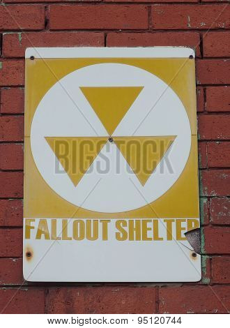 An Old Fallout Shelter Sign on A Brick Wall