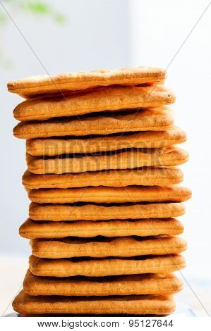 Freshly baked cheese based biscuits stacked on top of one another on a plain background