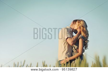 Stunning Sensual Young Couple In Love Embracing At The Sunset In Summer Field