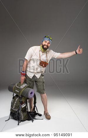 Full length view of male tourist with backpack hitchhiking on gray background poster