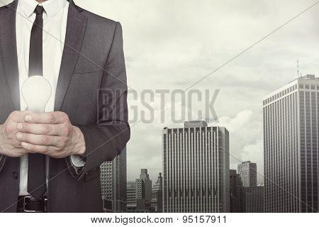 Businessman holding light bulb in hands