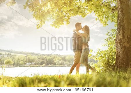 Couple in love on the lake beneath the trees kissing